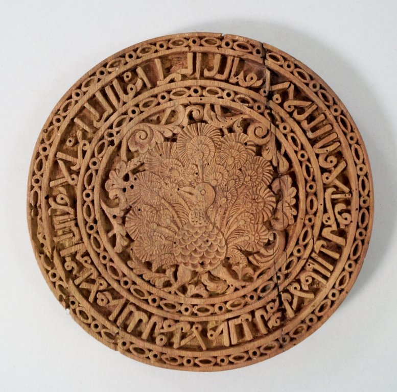 A Spanish circular wooden plaque, carved to the edge