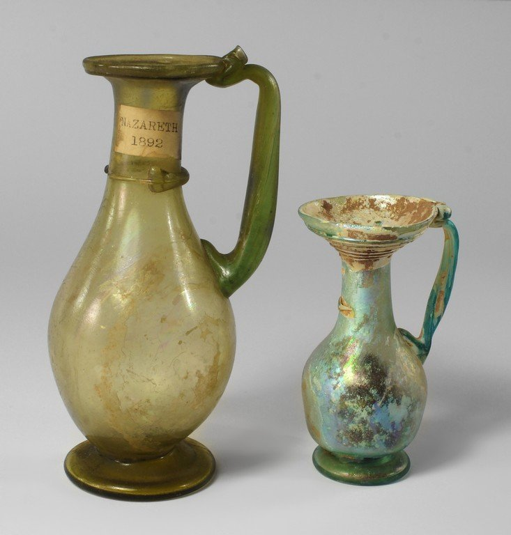A Roman pale blue glass jug, 2nd century AD, with wide