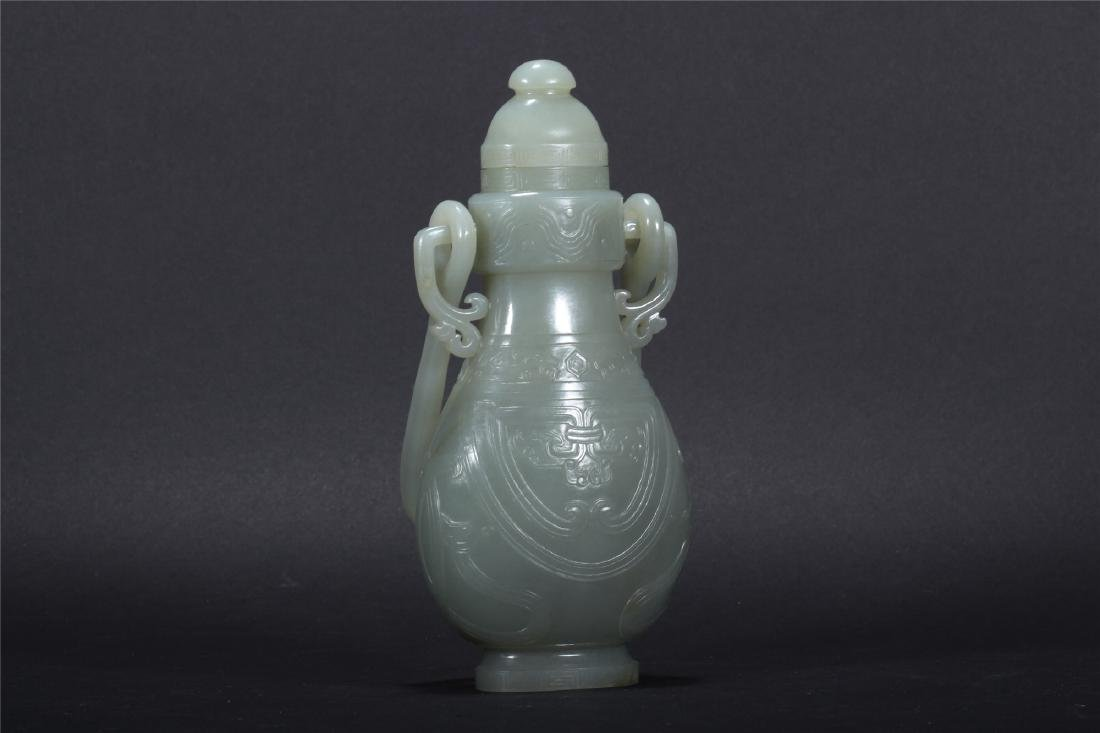 A CHINESE PALE CELADON JADE VASE WITH OVER-HANGING