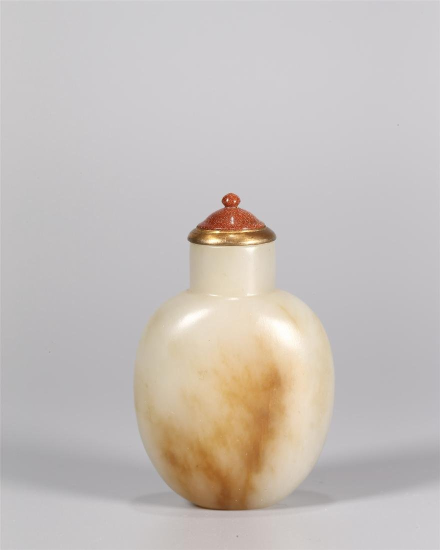 A CHINESE PALE WHITE AND RUSSET JADE SNUFF BOTTLE