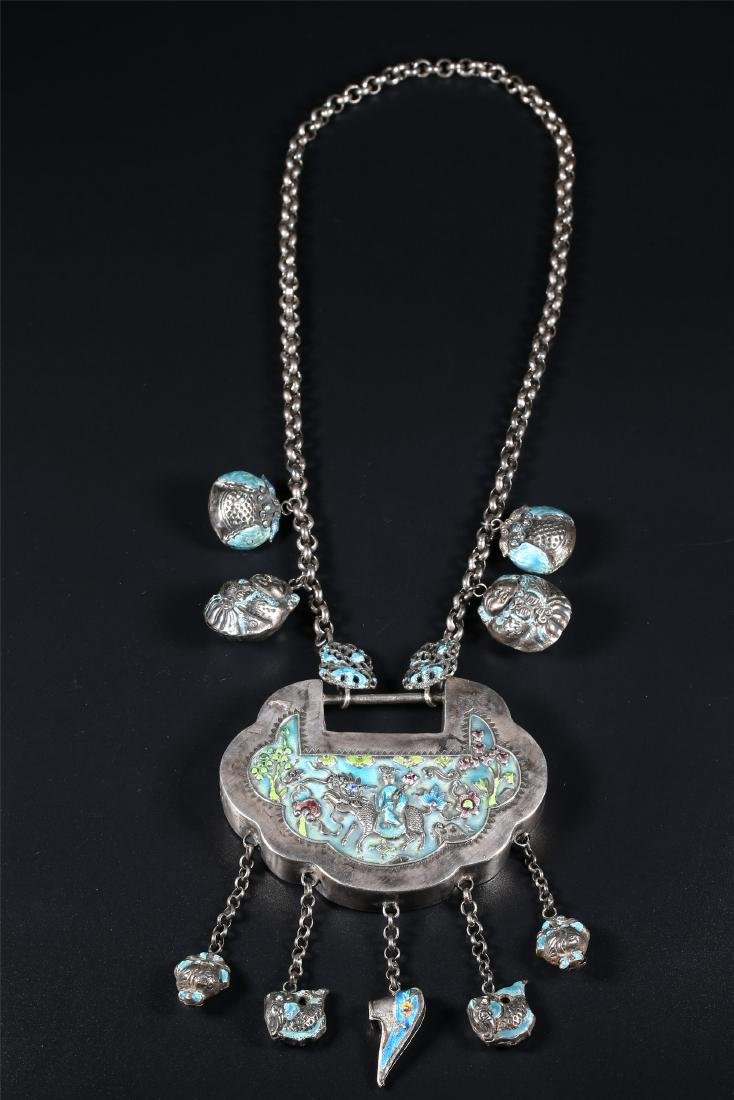 A CHINESE SILVER AMULET AND NECKLACE