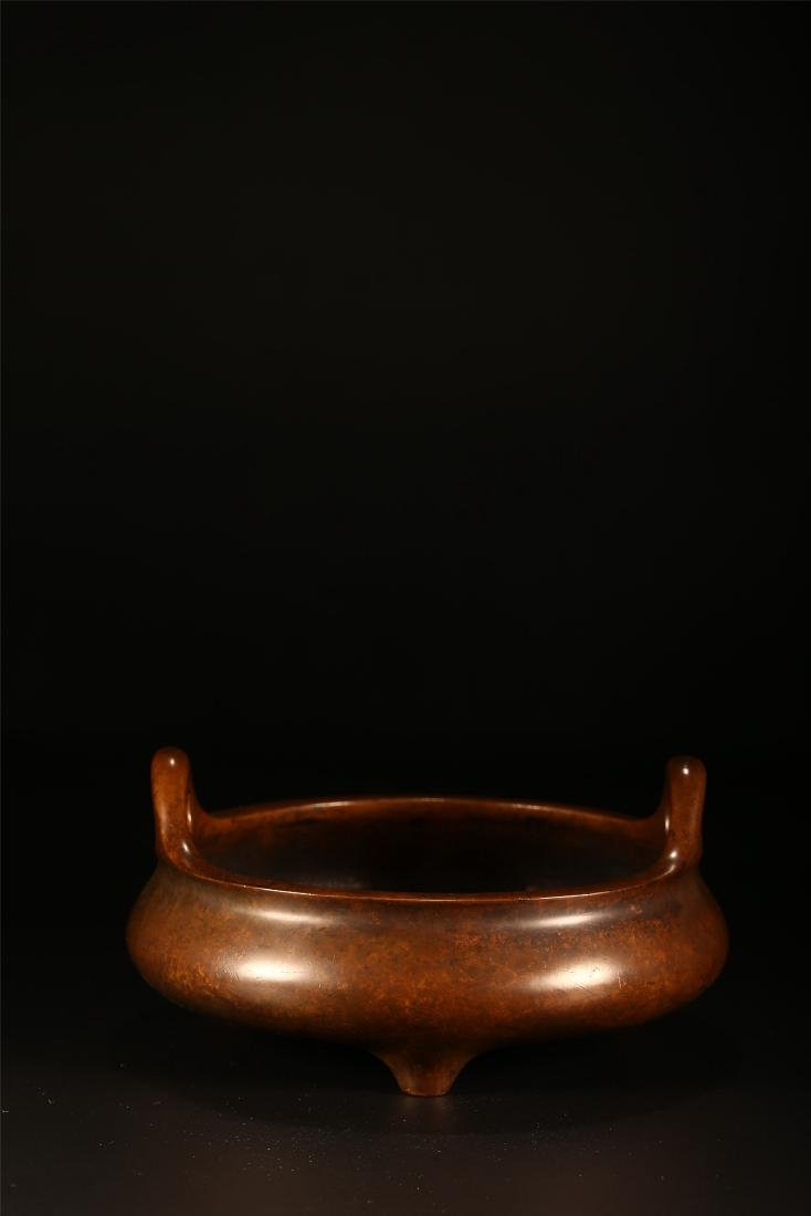 A CHINESE BRONZE DOUBLE HANDLED TRIPOD CENSER