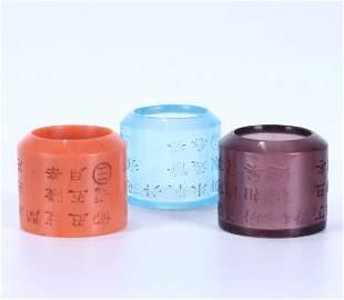 THREE INSCRIBED PEKING GLASS THUMB RINGS