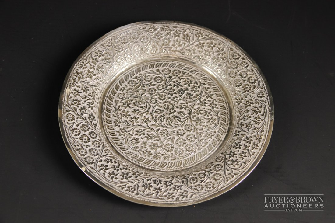 An Indian white metal circular tray, foliate and floral