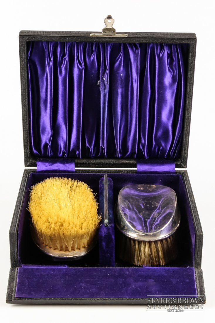 A set of two silver backed brushes, with a silver