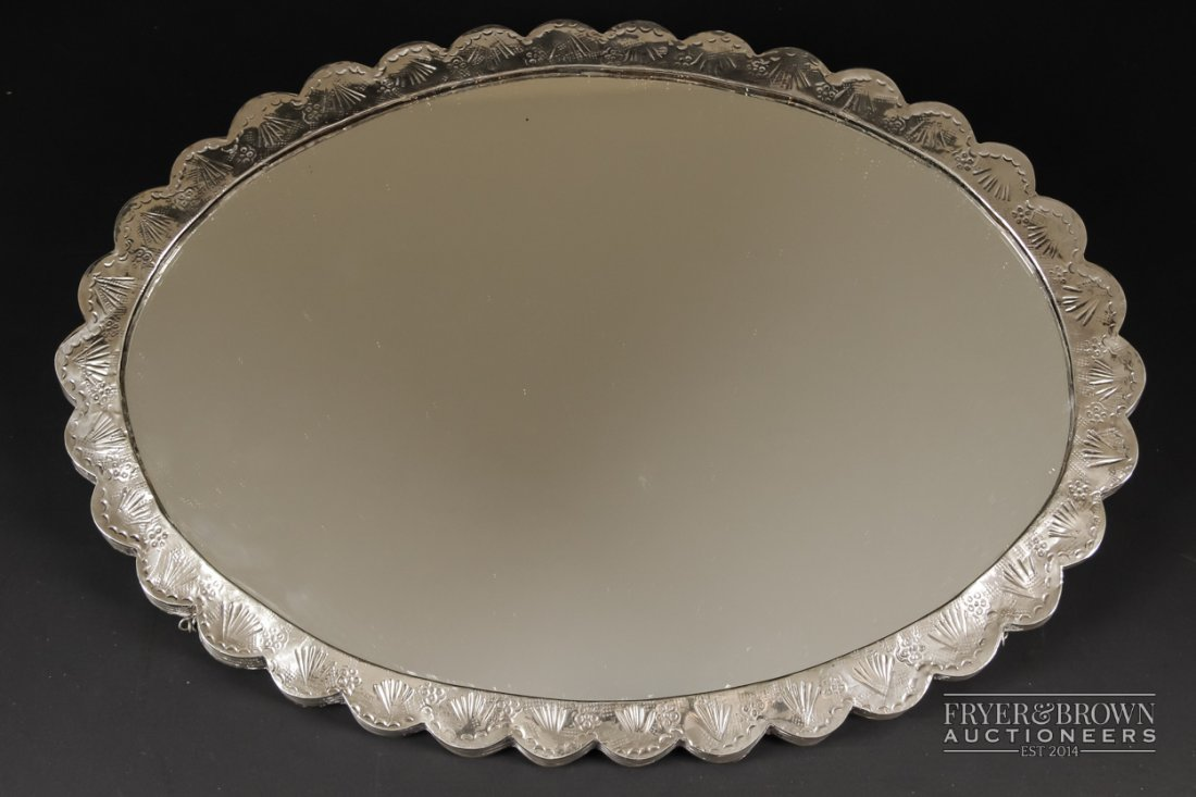 A Turkish silver modesty mirror, oval with scalloped