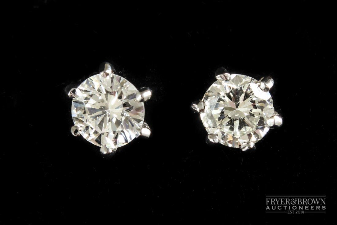 A pair of single stone diamond earrings, weighing