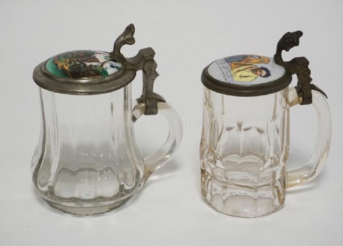 LOT OF 2 GLASS STEINS WITH PORCELAIN LIDS. ONE IS BLOWN