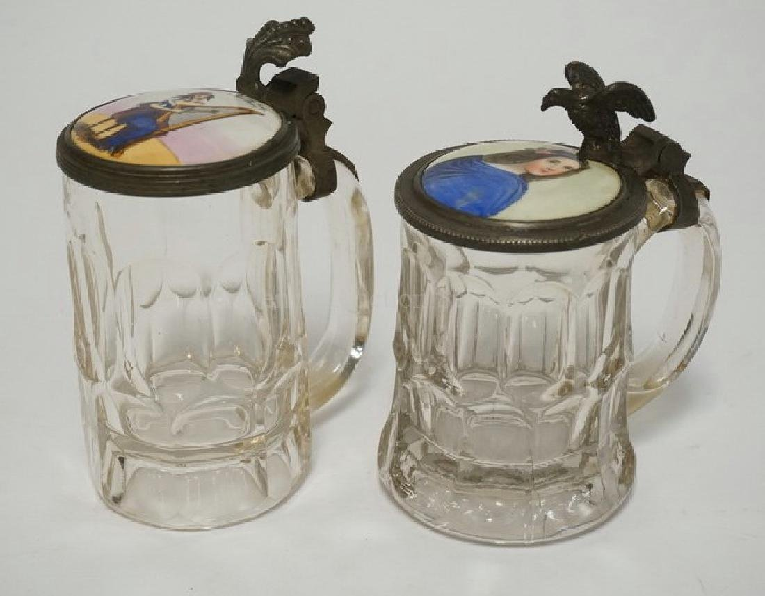 PAIR OF GLASS STEINS WITH PAINTED PORCELAIN LIDS