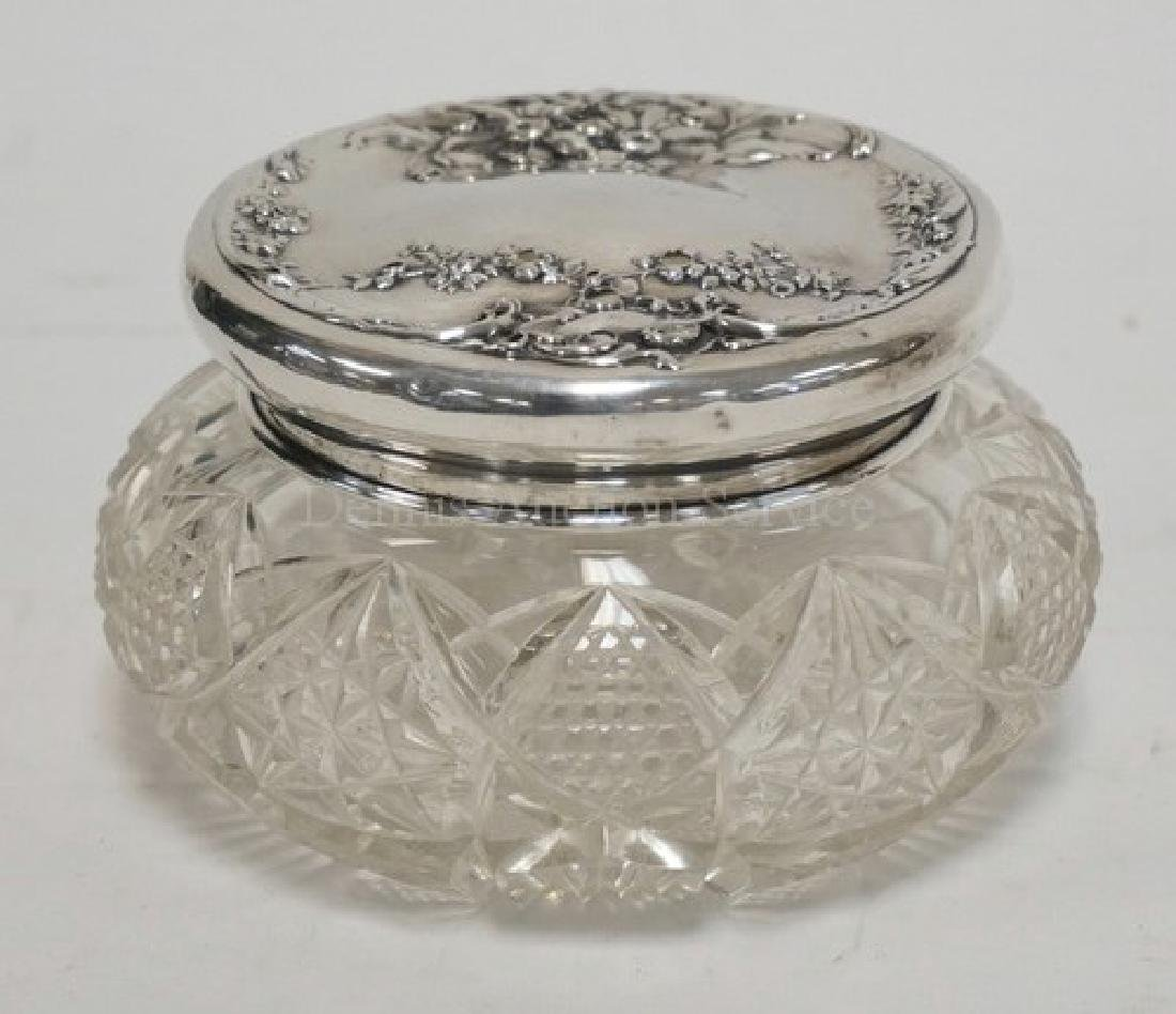 CUT GLASS DRESSER BOX WITH A STERLING SILVER LID.