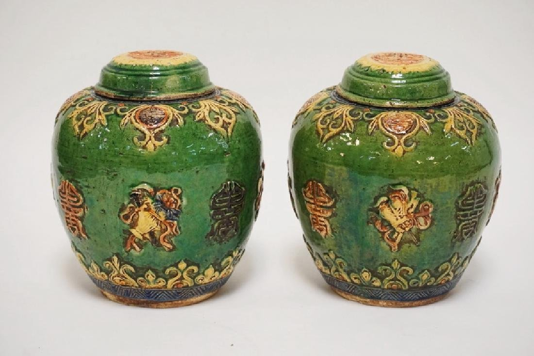 PAIR OF ASIAN POTTERY LIDDED JARS. POLYCROME DECORATED.
