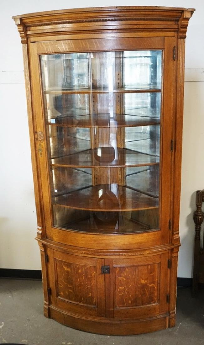 OAK BUILT-IN CORNER CABINET WITH A BOWED GLASS DOOR AND