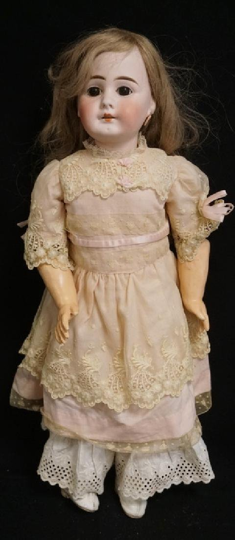 GERMAN BISQUE HEAD DOLL MEASURING 22 INCHES LONG.