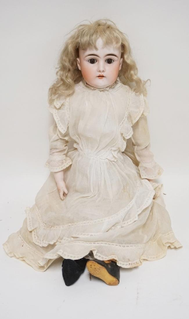 BISQUE HEADED DOLL MEASURING 22 INCHES HIGH. IMPRESSED