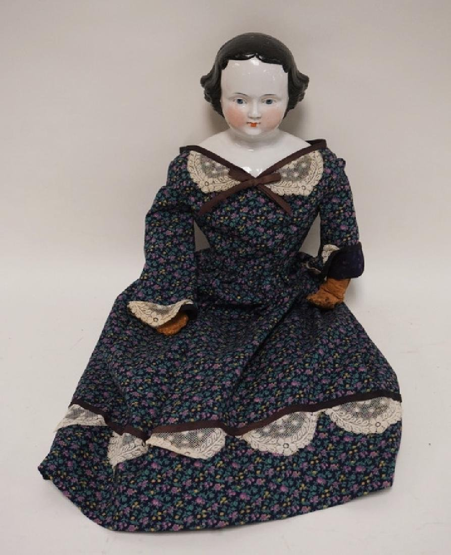 CHINA HEAD DOLL WITH LEATHER ARMS. 25 INCHES TALL.