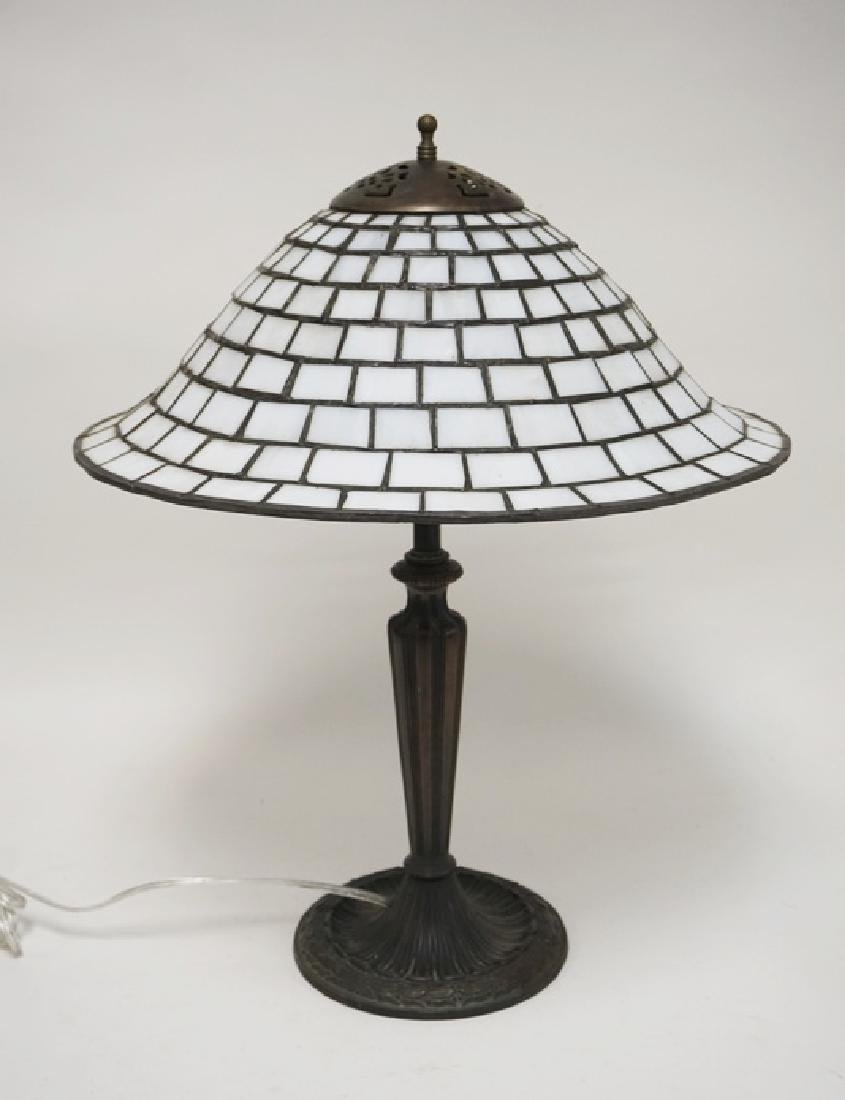 LEADED TABLE LAMP WITH A WHITE METAL BASE. THE BASE IS