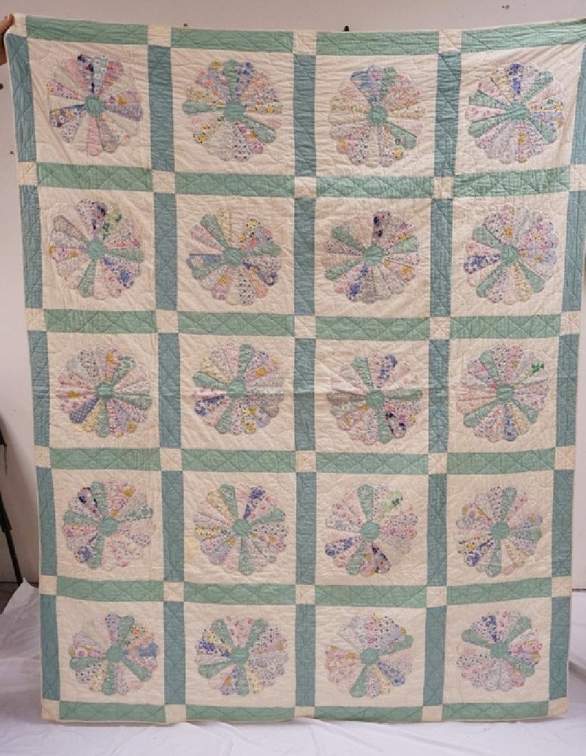 HAND STITCHED QUILT IN A DRESDEN PLATE PATTERN.