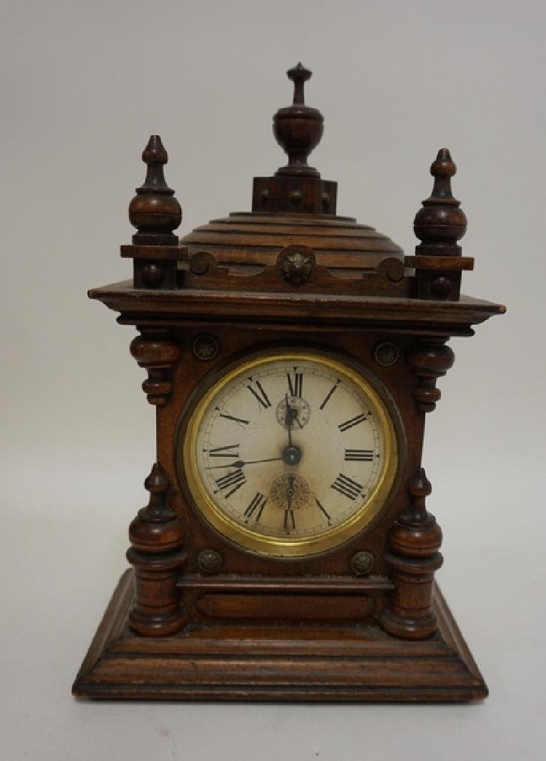 JUNGHANS VICTORIAN CLOCK IN CARVED CASE. 7 1/2 IN WIDE,