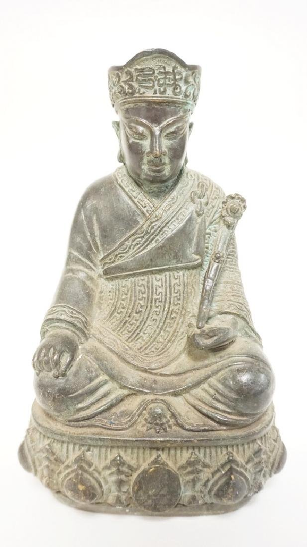 ASIAN BRONZE SEATED FIGURE HOLDING A RUYI. BASE CEMENT