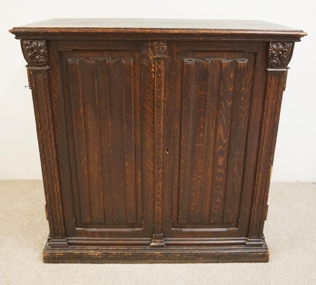 ANTIQUE CARVED OAK CABINET WITH SCROLL DECORATED DOORS.