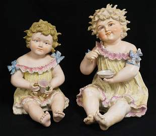 PAIR OF LARGE BISQUE PORCELAIN PIANO BABIES. TALLEST IS