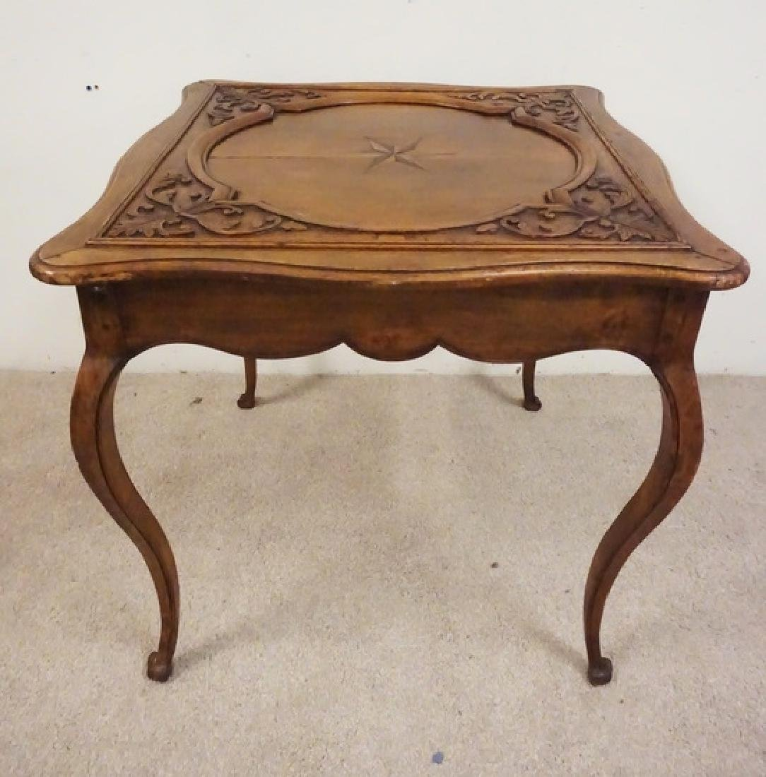 CARVED AND INLAID TABLE WITH A SCROLL CUT SKIRT.