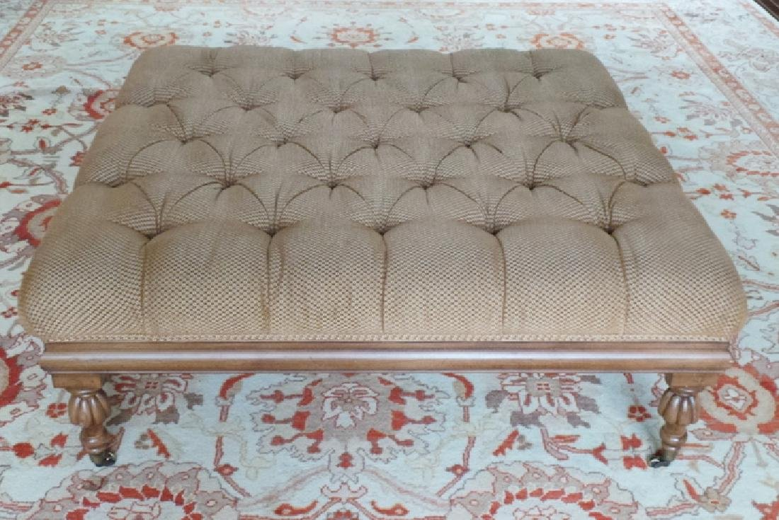 OTTOMAN WITH TUFTED UPHOLSTERY AND CARVED LEGS.