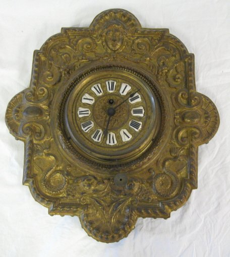 2010: CLOCK; BRASS EMBOSSED ON WOOD FIGURAL HANGING WAL