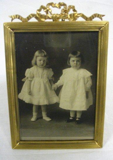 """11: BRONZE FRAME W/ BOW CREST. PHOTO OF 2 CHILDREN, 7"""""""