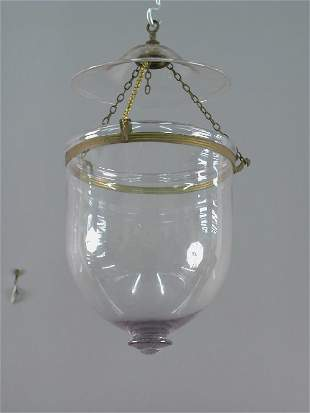 A colorless glass hall lantern with brass bird-