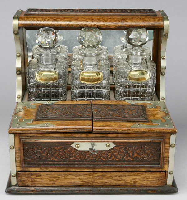 7: An oak English 3 bottle tantalus with game drawer
