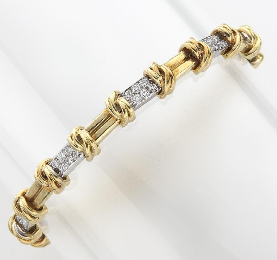 Platinum, 18K gold and diamond link bracelet.