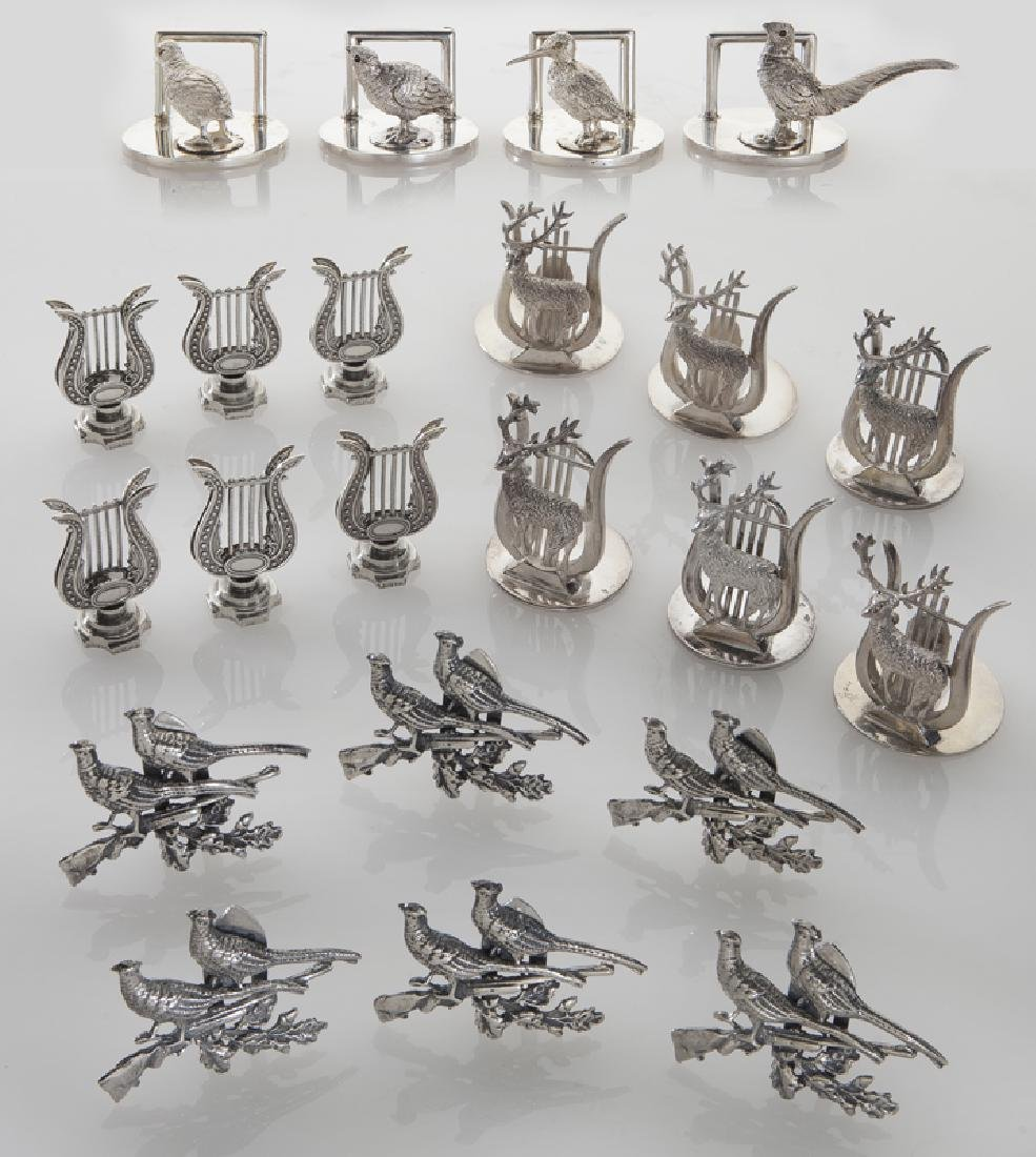 Four sets of silver place card holders;