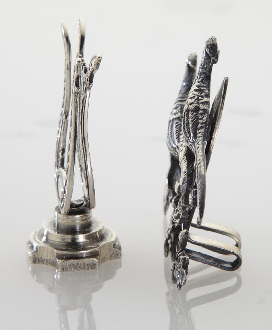 Four sets of silver place card holders; - 3