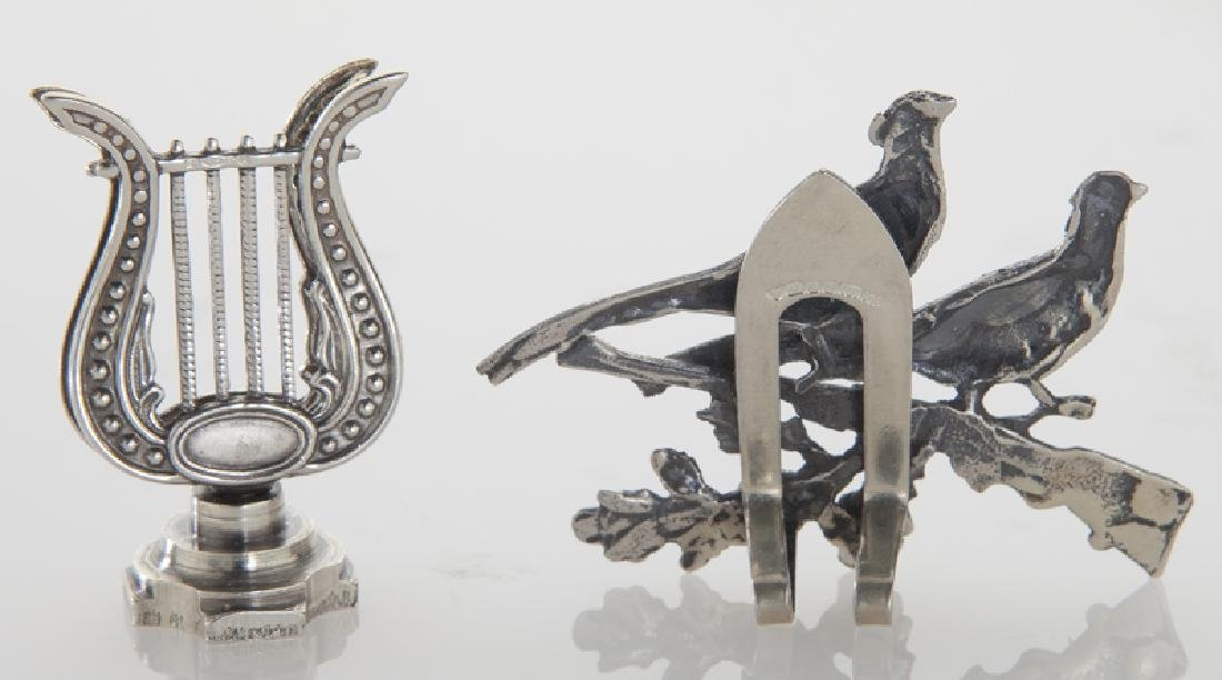 Four sets of silver place card holders; - 4