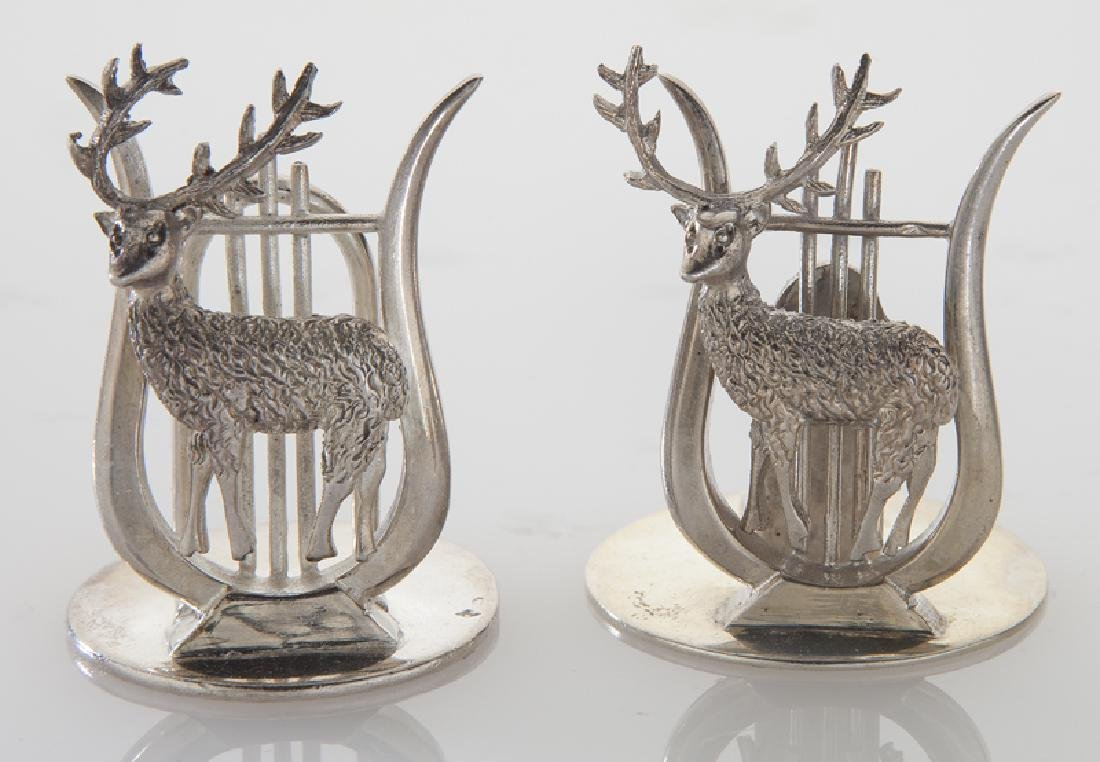 Four sets of silver place card holders; - 6