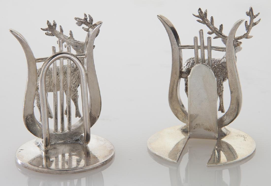 Four sets of silver place card holders; - 8