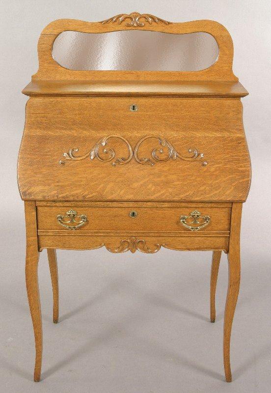 23: American oak slant lid desk having a shaped crest