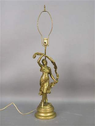 A gilt lamp with a figure of a dancing