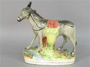 Staffordshire figure of a burro with yel