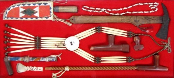 650: Frame with Sioux Calinite pipes, breastplate, axe,