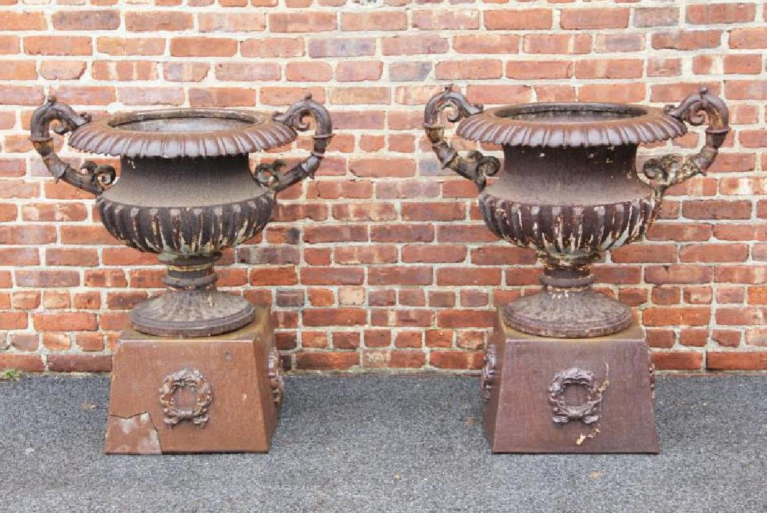 Pair Of Antique Cast Iron Urns On Stands .