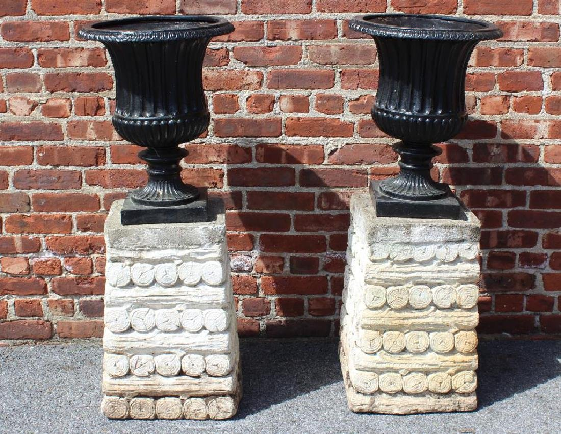 Pair of Cast Iron Urns on Painted Portland Bases.