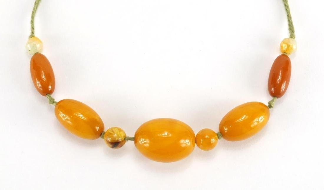 Butterscotch amber coloured bead necklace, the largest bead 3cm in length, approximate weight 34.