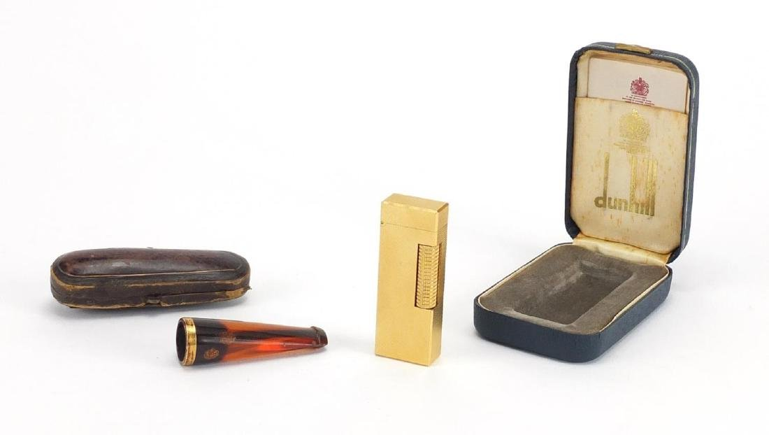 Gold plated Dunhill pocket lighter and cheroot with gold coloured metal mount, both with fitted