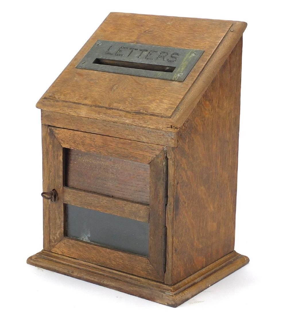 Edwardian oak letter box with hinged front having a brass 'Letters' flap above a glass panel, 30cm