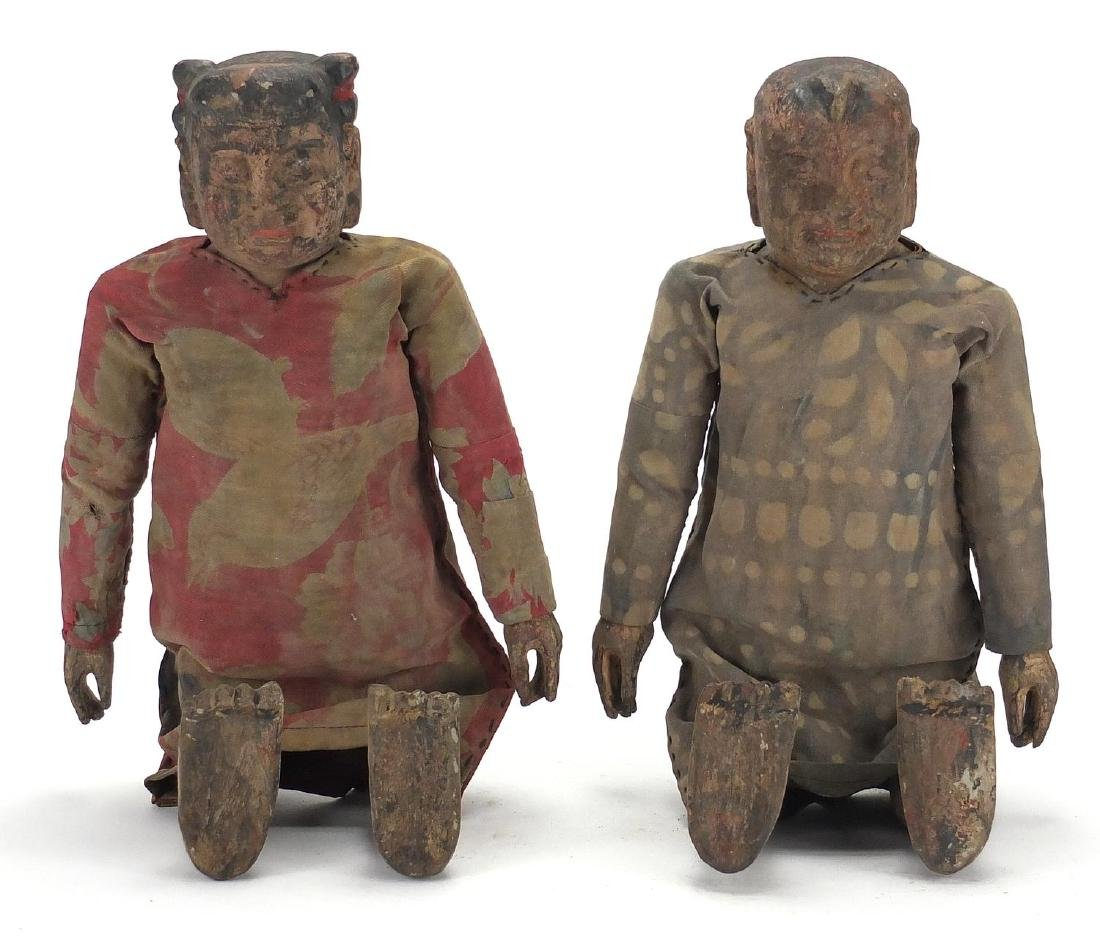Pair of Chinese lacquered and carved wood puppets, both with cloth dresses, each approximately