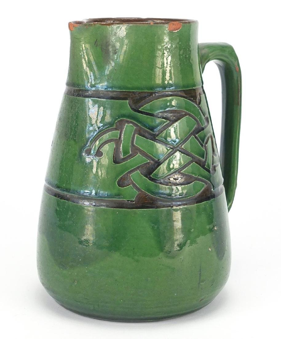 C H Brannam pottery jug made for Liberty & Co, incised with a Celtic design, impressed marks to