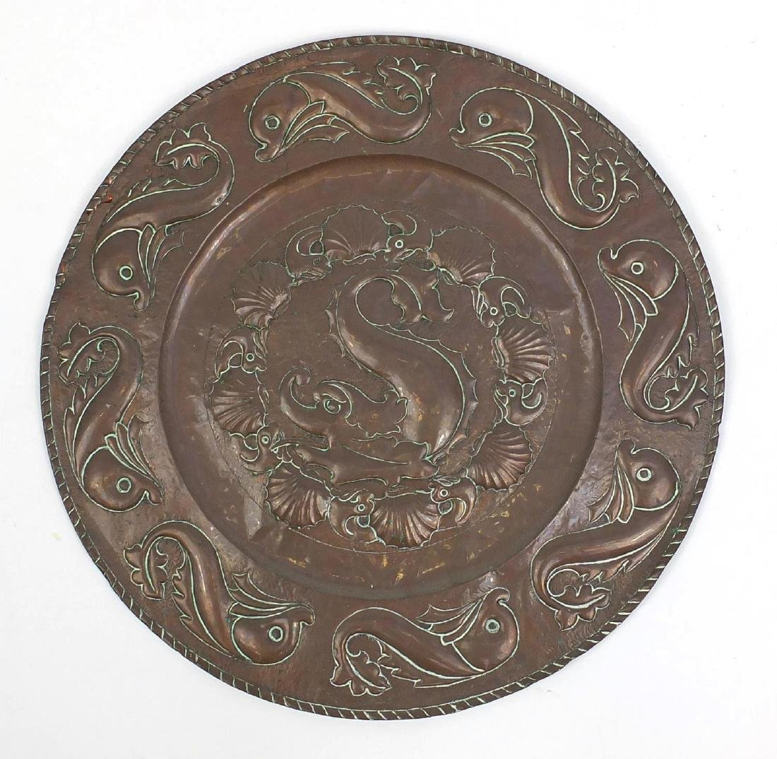 Large Arts & Crafts copper charger embossed with stylised dolphins, 64cm in diameter Further