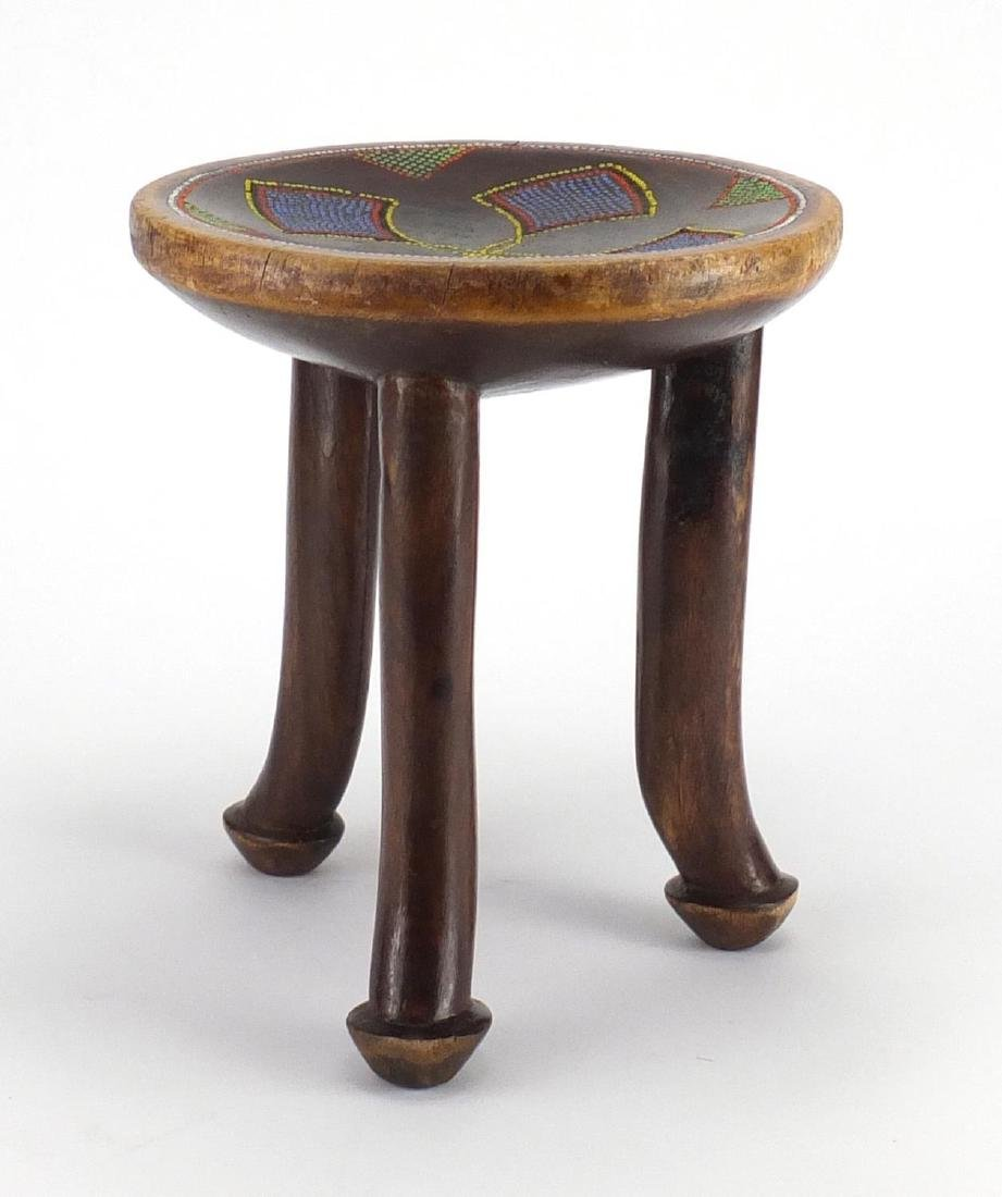 African hardwood stool with inset beadwork, 25cm high Further condition reports can be found at